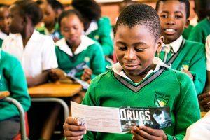 Student školy v Jihoafrické republice čte materiály kampaně o účincích drog